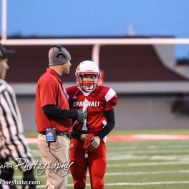 Hoisington Cardinal Head Coach Zach Baird gives the next play to Tyler Specht (#1) during the Hoisington High School versus Smoky Valley football game with Hoisington winning 33 to 12 at Eldon Brown Field in Hoisington, Kansas on October 10, 2014. (Photo: Joey Bahr, www.joeybahr.com)