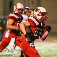 Hoisington Cardinal Hunter Hanzlick (#27) rushes down the field with the ball during the Hoisington High School versus Smoky Valley football game with Hoisington winning 33 to 12 at Eldon Brown Field in Hoisington, Kansas on October 10, 2014. (Photo: Joey Bahr, www.joeybahr.com)