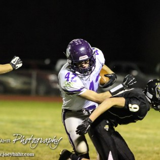 Meade Buffalo Ryan Friesen (#42) pushes LaCrosse Leopard Chase Klozenbucher (#9) out of the way during the KSHSAA Class 2-1A Regional Football game with Meade at LaCrosse with LaCrosse winning 34 to 0 at Bill Schoendaller Athletic Field in LaCrosse, Kansas on November 7, 2014. (Photo: Joey Bahr, www.joeybahr.com)