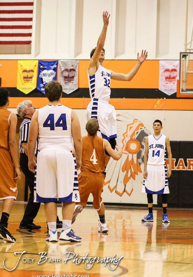 St. John Tiger Dean Wade (#32) goes high for the opening tip-off during the Seventh Annual Keady Basketball Classic First Round game between the St. John Tigers and the Kiowa County Mavericks with St. John winning 74 to 30 at Larned Middle School in Larned, Kansas on December 9, 2014. (Photo: Joey Bahr, www.joeybahr.com)