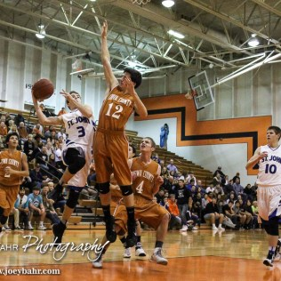 St. John Tiger Quincy Smith (#3) goes for a layup as Kiowa County Maverick Nicholas Sears (#12) defends during the Seventh Annual Keady Basketball Classic First Round game between the St. John Tigers and the Kiowa County Mavericks with St. John winning 74 to 30 at Larned Middle School in Larned, Kansas on December 9, 2014. (Photo: Joey Bahr, www.joeybahr.com)