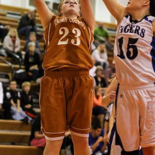 Kiowa County Lady Maverick Tierra West (#23) goes for a layup as St. John Lady Tiger Tara Christie (#15) defends during the Seventh Annual Keady Basketball Classic First Round game between the St. John Lady Tigers and the Kiowa County Lady Mavericks with St. John winning 47 to 31 at Larned Middle School in Larned, Kansas on December 9, 2014. (Photo: Joey Bahr, www.joeybahr.com)