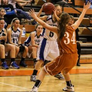 St. John Lady Tiger Kerisa Brown (#5) looks for a teammate to pass the ball to during the Seventh Annual Keady Basketball Classic First Round game between the St. John Lady Tigers and the Kiowa County Lady Mavericks with St. John winning 47 to 31 at Larned Middle School in Larned, Kansas on December 9, 2014. (Photo: Joey Bahr, www.joeybahr.com)