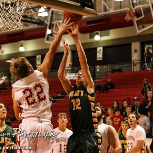Hoisington Cardinal Grant Dolechek (#22) blocks the shot of Pratt Greenback Brandon Ruckle (#12) during the Pratt Greenbacks at Hoisington Cardinals Boys Basketball game with Pratt winning 66 to 34 at Hoisington Activity Center in Hoisington, Kansas on January 6, 2015. (Photo: Joey Bahr, www.joeybahr.com)