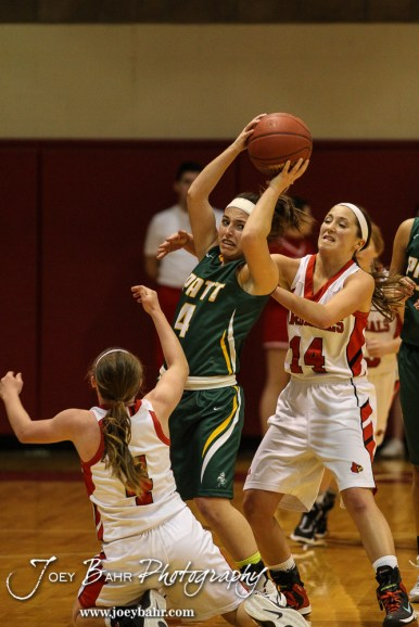 Pratt Lady Greenback Brooklynn Bourgeois (#4) pulls away a loose ball from Hoisington Lady Cardinal Karisa Schremmer (#4) during the Pratt Lady Greenbacks at Hoisington Lady Cardinals Girls Basketball game with Pratt winning 34 to 23 at Hoisington Activity Center in Hoisington, Kansas on January 6, 2015. (Photo: Joey Bahr, www.joeybahr.com)