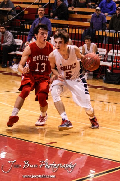 Hoisington Cardinal Corbin Crawford (#13) rides along with Minneapolis Lion Brandon Wolfe (#5) during the 2016 Hoisington Winter Jam Boys Championship Basketball game between the Hoisington Cardinals and the Minneapolis Lions with Hoisington winning 39 to 38 of Hoisington Activity Center in Hoisington, Kansas on January 23, 2016. (Photo: Joey Bahr, www.joeybahr.com)