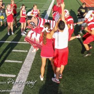 The Hoisington Cardinals run through a banner prior to the Hoisington Cardinal versus Larned Indian Football game with Hoisington winning 53 to 21 at Elton Brown Field in Hoisington, Kansas on September 4, 2015. (Photo: Joey Bahr, www.joeybahr.com)