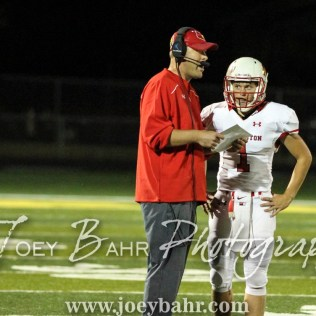 Hoisington Cardinal Head Coach Zach Baird gives the next play to Tyler Specht (#1). The Hoisington Cardinals defeated the Pratt Greenbacks 32 to 14 at Zerger Field in Pratt, Kansas on September 30, 2016. (Photo: Joey Bahr, www.joeybahr.com)