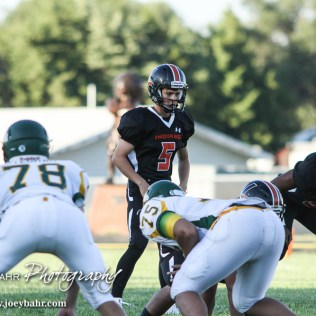 Larned Indian Carson Smith (#5) looks over the defense. The Pratt Greenbacks win 31 to 16 over the Larned Indians at Earl Roberts Field in Larned, Kansas on September 2, 2016. (Photo: Joey Bahr, www.joeybahr.com)