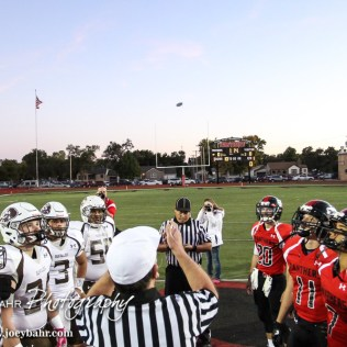 The Head Referee tosses the coin before the game as the team captains watch. The Garden City Buffaloes defeated the Great Bend Panthers 21 to 14 in Overtime to win the Western Athletic Conference title at Memorial Stadium in Great Bend, Kansas on October 21, 2016. (Photo: Joey Bahr, www.joeybahr.com)