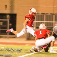 Hoisington Cardinal Tyler Specht (#1) holds the ball as Inigo Barrena Carpio (#8) kicks a Point After Touchdown. The Hoisington Cardinals defeated the Lyons Lions to win the KSHSAA Class 3A District 15 Championship at Elton Brown Field in Hoisington, Kansas on October 27, 2016. (Photo: Joey Bahr, www.joeybahr.com)