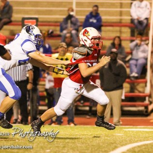 Lyons Lion Connor Crawford (#60) holds the jersey of Hoisington Cardinal Jeremy Breit (#60) as he comes through the line. The Hoisington Cardinals defeated the Lyons Lions to win the KSHSAA Class 3A District 15 Championship at Elton Brown Field in Hoisington, Kansas on October 27, 2016. (Photo: Joey Bahr, www.joeybahr.com)