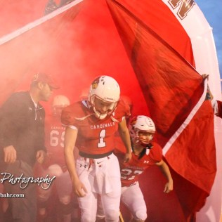 Hoisington Cardinal Tyler Specht (#1) leads his teammates onto the field. The Hoisington Cardinals defeated the Lakin Broncs in the KSHSAA Class 3A Bi-District game with a score of 56 to 13 at Elton Brown Field in Hoisington, Kansas on November 1, 2016. (Photo: Joey Bahr, www.joeybahr.com)