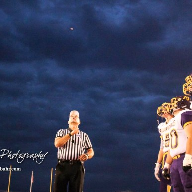 Captains from both teams watch as the coin is tossed in the air. The Hoisington Cardinals defeated the Lakin Broncs in the KSHSAA Class 3A Bi-District game with a score of 56 to 13 at Elton Brown Field in Hoisington, Kansas on November 1, 2016. (Photo: Joey Bahr, www.joeybahr.com)