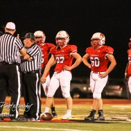 The Hoisington Cardinal Defense stands by as three officials discus why a flag was thrown. The Hoisington Cardinals defeated the Lakin Broncs in the KSHSAA Class 3A Bi-District game with a score of 56 to 13 at Elton Brown Field in Hoisington, Kansas on November 1, 2016. (Photo: Joey Bahr, www.joeybahr.com)