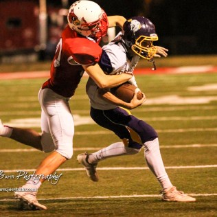 Hoisington Cardinal Hunter Hanzlick (#27) tackles Lakin Bronc Hunter Kirby (#5). The Hoisington Cardinals defeated the Lakin Broncs in the KSHSAA Class 3A Bi-District game with a score of 56 to 13 at Elton Brown Field in Hoisington, Kansas on November 1, 2016. (Photo: Joey Bahr, www.joeybahr.com)