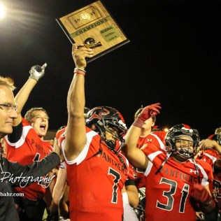 Great Bend Panther Jacob Murray (#7) holds up the Class 5A Regional Champion Trophy. The Great Bend Panthers defeated the Andover Trojans in the KSHSAA Class 5A Regional playoff game with a score of 16 to 7 at Memorial Stadium in Great Bend, Kansas on November 4, 2016. (Photo: Joey Bahr, www.joeybahr.com)