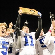 Goddard Lions Thomas Parks (#55), Blake Sullivan (#11), and Matt Forbus (#15) celebrate with the Sub-State Champion Trophy. The Goddard Lions defeated the Great Bend Panthers to win the KSHSAA Class 5A Sub-State Championship by a score of 50 to 21 at Memorial Field in Great Bend, Kansas on November 18, 2016. (Photo: Joey Bahr, www.joeybahr.com)