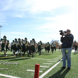 Dan Page of KWCH videos the Pratt Greenbacks taking the field prior to the game. The Pratt Greenbacks defeated the Hayden Wildcats 48 to 14 to win the KSHSAA Class 4A Division II State Championship Game at Salina Stadium in Salina, Kansas on November 26, 2016. (Photo: Joey Bahr, www.joeybahr.com)