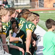 The Pratt Greenback sideline takes a knee as an injured teammate is tended to. The Pratt Greenbacks defeated the Hayden Wildcats 48 to 14 to win the KSHSAA Class 4A Division II State Championship Game at Salina Stadium in Salina, Kansas on November 26, 2016. (Photo: Joey Bahr, www.joeybahr.com)