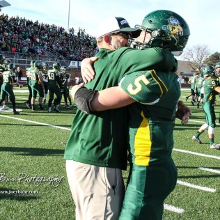 Pratt Greenback Travis Theis (#5) and his Head Coach Jamie Cruce hug following the game. The Pratt Greenbacks defeated the Hayden Wildcats 48 to 14 to win the KSHSAA Class 4A Division II State Championship Game at Salina Stadium in Salina, Kansas on November 26, 2016. (Photo: Joey Bahr, www.joeybahr.com)