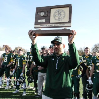 Pratt Greenback Head Coach Jamie Cruce holds the State Championship Trophy aloft. The Pratt Greenbacks defeated the Hayden Wildcats 48 to 14 to win the KSHSAA Class 4A Division II State Championship Game at Salina Stadium in Salina, Kansas on November 26, 2016. (Photo: Joey Bahr, www.joeybahr.com)