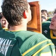 Pratt Greenback Bryce Stegman (#78) kisses the State Championship Trophy. The Pratt Greenbacks defeated the Hayden Wildcats 48 to 14 to win the KSHSAA Class 4A Division II State Championship Game at Salina Stadium in Salina, Kansas on November 26, 2016. (Photo: Joey Bahr, www.joeybahr.com)
