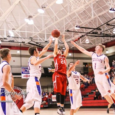 Hoisington Cardinal #24 Eric Barrett shoots a jump shot as Otis-Bison Cougars #33 Anton Foust and #1 Blake Bahr try to block it. The Hoisington Cardinals defeated Otis-Bison Cougars 56 to 39 in the Boys Semi-Final of the 2017 Hoisington Winter Jam at Hoisington Activity Center in Hoisington, Kansas on January 20, 2017. (Photo: Joey Bahr, www.joeybahr.com)