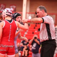 An official holds up the hand of Mya Kretzer (McPherson) after she defeated Sunny O`Leary (Riley County) by fall. The first ever Kansas High School Girls Wrestling Championship was held at the Roundhouse at McPherson High School in McPherson, Kansas on February 11, 2017. (Photo: Joey Bahr, www.joeybahr.com)