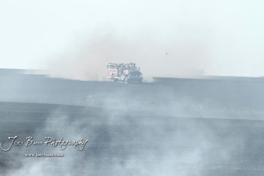 A truck from the Hoisington Fire Department travels down a burned out section of the field. Members of the Olmitz, Hoisington, and Galatia Fire Departments respond to a controlled burn that got out of control two miles north of the junction of Kansas Highway 4 and US Highway 281 near Hoisington, Kansas on July 1, 2017. (Photo: Joey Bahr, www.joeybahr.com)