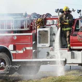 A firefighter with the Hoisington Fire Department works to put out the fire that had spread to the ditch alongside US Highway 281. Members of the Olmitz, Hoisington, and Galatia Fire Departments respond to a controlled burn that got out of control two miles north of the junction of Kansas Highway 4 and US Highway 281 near Hoisington, Kansas on July 1, 2017. (Photo: Joey Bahr, www.joeybahr.com)