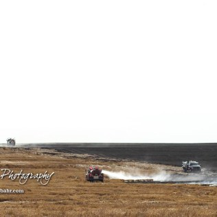 Multiple trucks work on hotspots on the south side of the stubble field fire. Members of the Olmitz, Hoisington, and Galatia Fire Departments respond to a controlled burn that got out of control two miles north of the junction of Kansas Highway 4 and US Highway 281 near Hoisington, Kansas on July 1, 2017. (Photo: Joey Bahr, www.joeybahr.com)
