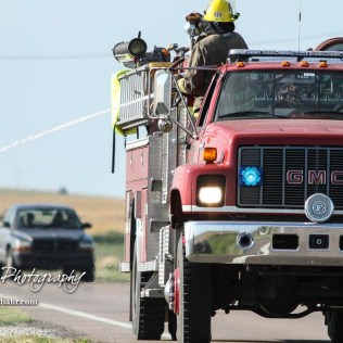 A vehicle traveling on US Highway 281 passes behind a truck from the Hoisington Fire Department spraying a hot spot in the ditch. Members of the Olmitz, Hoisington, and Galatia Fire Departments respond to a controlled burn that got out of control two miles north of the junction of Kansas Highway 4 and US Highway 281 near Hoisington, Kansas on July 1, 2017. (Photo: Joey Bahr, www.joeybahr.com)