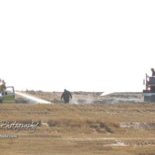 Two fire trucks and a dismounted firefighter battle a hotspot in the field. Members of the Olmitz, Hoisington, and Galatia Fire Departments respond to a controlled burn that got out of control two miles north of the junction of Kansas Highway 4 and US Highway 281 near Hoisington, Kansas on July 1, 2017. (Photo: Joey Bahr, www.joeybahr.com)