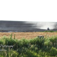 Cory Wagner, farmer of the burned field, travels down the hill towards the edge of the property. Members of the Olmitz, Hoisington, and Galatia Fire Departments respond to a controlled burn that got out of control two miles north of the junction of Kansas Highway 4 and US Highway 281 near Hoisington, Kansas on July 1, 2017. (Photo: Joey Bahr, www.joeybahr.com)