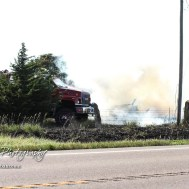 A truck moves towards a burning wood pile in the corner of the property. Members of the Olmitz, Hoisington, and Galatia Fire Departments respond to a controlled burn that got out of control two miles north of the junction of Kansas Highway 4 and US Highway 281 near Hoisington, Kansas on July 1, 2017. (Photo: Joey Bahr, www.joeybahr.com)