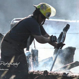 A firefighter uses a crow bar to move over a log while searching for embers and hotspots in a wood pile. Members of the Olmitz, Hoisington, and Galatia Fire Departments respond to a controlled burn that got out of control two miles north of the junction of Kansas Highway 4 and US Highway 281 near Hoisington, Kansas on July 1, 2017. (Photo: Joey Bahr, www.joeybahr.com)