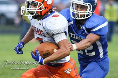 Otis-Bison Cougar #8 Daniel Scott runs with the ball as St. John Tiger #22 Keven Neri Leon reaches out to tackle him in the second quarter. The Otis-Bison Cougars defeated the St. John Tigers by a score of 58 to 0 at St. John High School in St. John, Kansas on September 1, 2017. (Photo: Joey Bahr, www.joeybahr.com)