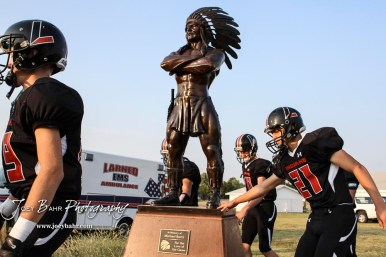 Larned Indian Austin Gladow (#21) touches the base of the Indian statue prior to walking on the field before the start of the game. The Larned Indians defeated the Smoky Valley Vikings by a score of 28 to 14 at Earl Roberts Stadium in Larned, Kansas on September 8, 2017. (Photo: Joey Bahr, www.joeybahr.com)