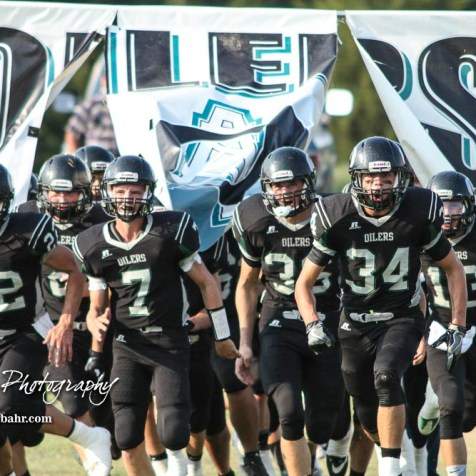 The Central Plains Oilers run through a banner to take the field to resume the delayed game. The Victoria Knights defeated the Central Plains Oilers by a score of 34 to 8 at Central Plains High School in Claflin, Kansas on September 2, 2017. (Photo: Joey Bahr, www.joeybahr.com)