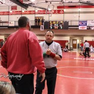 A Eureka coach discusses the score of a match with an official. The 2017 Cardinal Corner Classic Wrestling Tournament was held at Hoisington Activity Center in Hoisington, Kansas on December 15, 2017. (Photo: Joey Bahr, www.joeybahr.com)