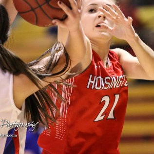Hoisington Lady Cardinal #21 Suzanna Schneider tries to tap the ball loose from the hands of Ellinwood Lady Eagle #22 Kennedy Harrington. The Hoisington Lady Cardinals defeated the Ellinwood Lady Eagles by a score of 46 to 19 in the Consolation Semi-Final of the 2018 Hoisington Winter Jam at the Hoisington Activity Center in Hoisington, Kansas on January 18, 2018. (Photo: Joey Bahr, www.joeybahr.com)