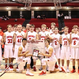 The Hoisington Cardinals pose with the championship trophy and bracket while holding up three fingers for their third consecutive tournament victory. The Hoisington Cardinals defeated the Pratt Greenbacks by a score of 47 to 41 in the Boys Championship game of the 2018 Hoisington Winter Jam at the Hoisington Activity Center in Hoisington, Kansas on January 20, 2018. (Photo: Joey Bahr, www.joeybahr.com)