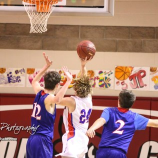 Ellinwood Eagle #24 Blake Garmam goes for a layup as Russell Bronco #12 Jacob Kraus defends. The Russell Broncos defeated the Ellinwood Eagles by a score of 60 to 17 in the Consolation Semi-Final of the 2018 Hoisington Winter Jam at the Hoisington Activity Center in Hoisington, Kansas on January 18, 2018. (Photo: Joey Bahr, www.joeybahr.com)