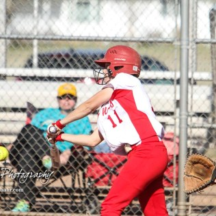 Hoisington Lady Cardinal Keeley Wolf (#11) swings at a pitch in the bottom of the sixth inning. The Hoisington Lady Cardinals defeated the Halstead Lady Dragons by a score of 12 to 2 in six innings at Logan Field in Hoisington, Kansas on April 27, 2018. (Photo: Joey Bahr, www.joeybahr.com)