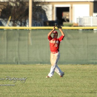 Hoisington Cardinal Jerred Bieberle (#13) catches a ball in the outfield in the top of the third inning. The Hoisington Cardinals defeated the Halstead Dragons by a score of 10 to 6 at Legion Field in Hoisington, Kansas on April 27, 2018. (Photo: Joey Bahr, www.joeybahr.com)