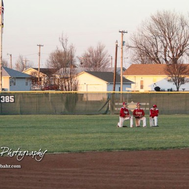 The Hoisington outfielders take a break as a new pitch warms up in the top of the fifth inning. The Hoisington Cardinals defeated the Halstead Dragons by a score of 10 to 6 at Legion Field in Hoisington, Kansas on April 27, 2018. (Photo: Joey Bahr, www.joeybahr.com)