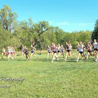 Competitors dash off of the starting line to begin the girls varsity race. The Great Bend Cross Country Invitational was held at Lake Barton near Great Bend, Kansas on August 30, 2018. (Photo: Joey Bahr, www.joeybahr.com)
