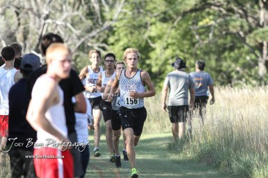 Garden City's Ethan Fisher (#156) leads a pack of runners out of a wooded section of the course. The Great Bend Cross Country Invitational was held at Lake Barton near Great Bend, Kansas on August 30, 2018. (Photo: Joey Bahr, www.joeybahr.com)