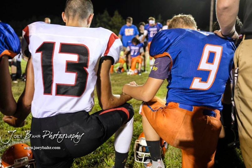Stafford Trojan #13 Ryan Sammons and Otis-Bison Cougar #9 Logan Thille holds hand during a post game prayer. The Otis-Bison Cougars defeated the Stafford Trojans by a score of 50 to 0 at Cougar Field in Otis, Kansas on September 14, 2018. (Photo: Joey Bahr, www.joeybahr.com)